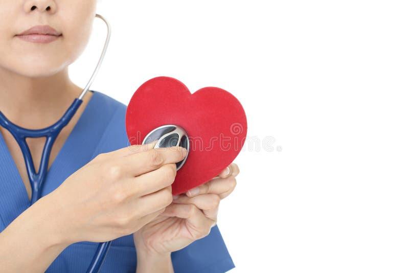 Doutor fêmea que guarda o símbolo vermelho do amor do coração fotografia de stock