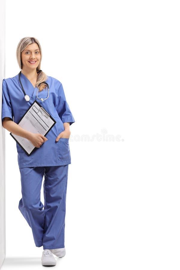 Doutor fêmea que guarda uma prancheta e que inclina-se contra uma parede imagens de stock royalty free