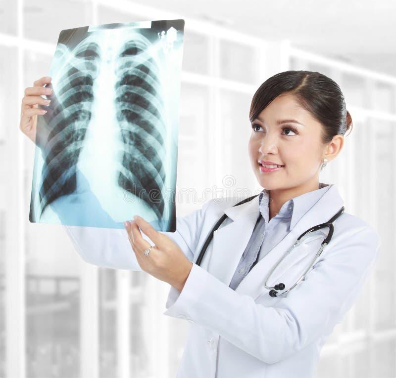 Doutor fêmea que olha um raio X fotos de stock