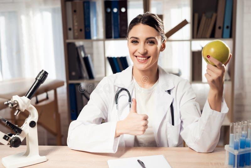 Doutor fêmea que senta-se na mesa no escritório com microscópio e estetoscópio A mulher está guardando a maçã amarela imagens de stock royalty free