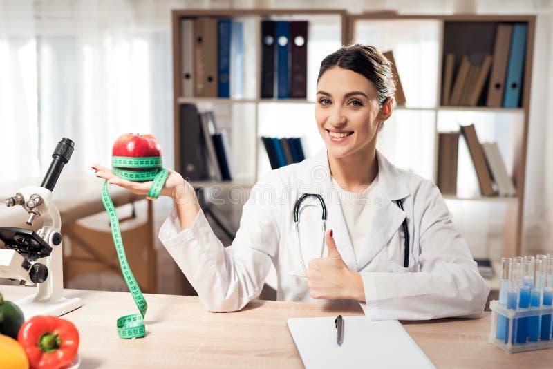 Doutor fêmea que senta-se na mesa no escritório com microscópio e estetoscópio A mulher está guardando a maçã vermelha com fita d foto de stock