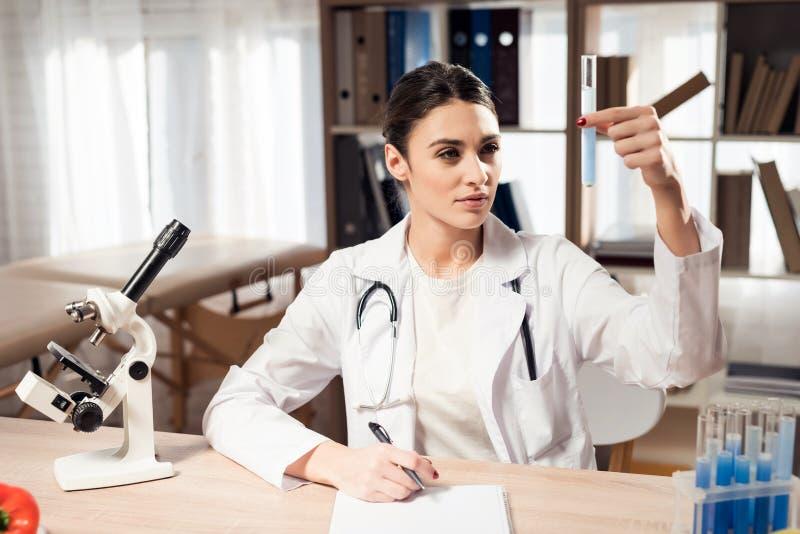 Doutor fêmea que senta-se na mesa no escritório com microscópio e estetoscópio A mulher está guardando a taça imagem de stock royalty free