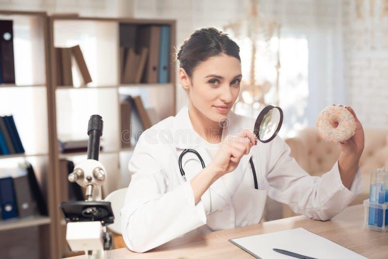 Doutor fêmea que senta-se na mesa no escritório com microscópio e estetoscópio A mulher está olhando a filhós com magnifyer imagem de stock