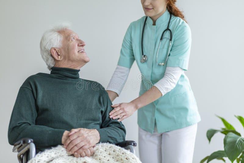 Doutor fêmea que toca em um braço de seu paciente em uma cadeira de rodas fotografia de stock royalty free