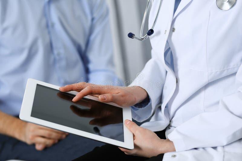 Doutor fêmea que usa o touchpad ou o tablet pc ao consultar o paciente do homem no hospital Medicina e cuidados médicos imagens de stock royalty free