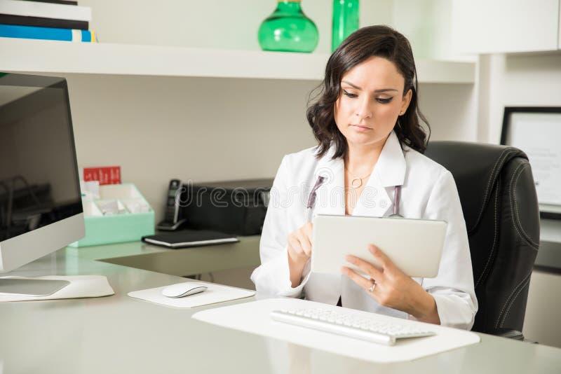 Doutor fêmea que usa a tecnologia em seu escritório fotografia de stock royalty free