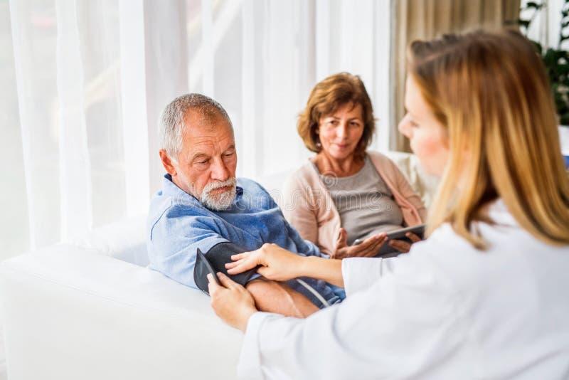 Doutor fêmea que verifica a pressão sanguínea do homem superior fotos de stock royalty free