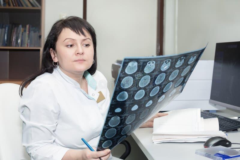 Doutor fêmea resultados de exame de um varredor do CT fotografia de stock
