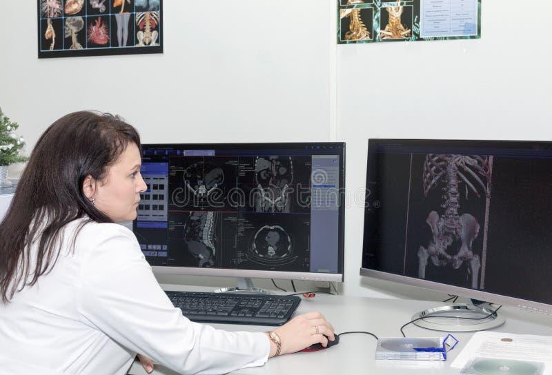Doutor fêmea resultados de exame de um varredor do CT imagem de stock