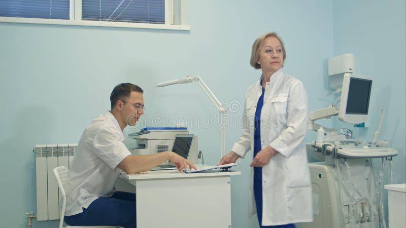 Doutor fêmea superior que compartilha de responsabilidades entre a equipa médica fotografia de stock