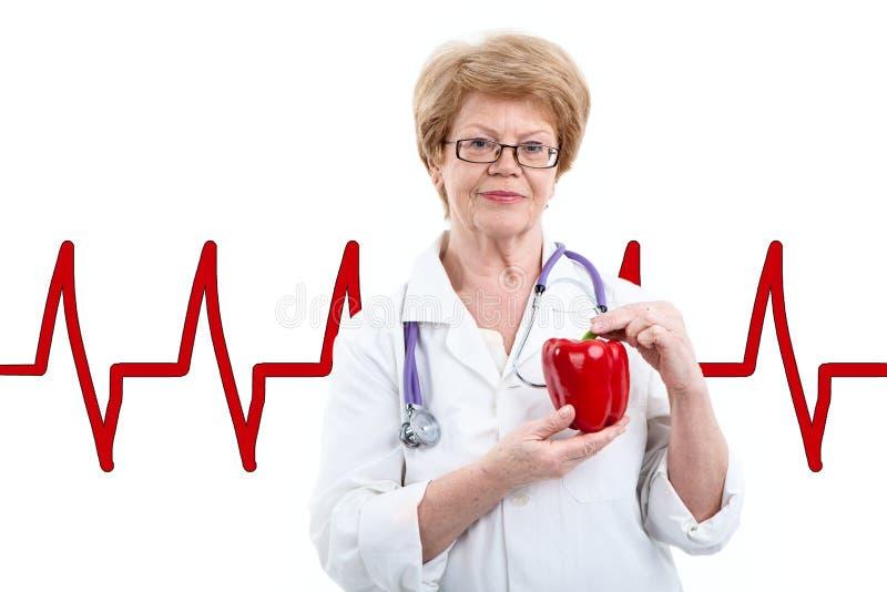 Doutor fêmea superior que guarda o papper doce vermelho nas mãos com linha da pulsação do coração no fundo, isolado no branco fotos de stock royalty free