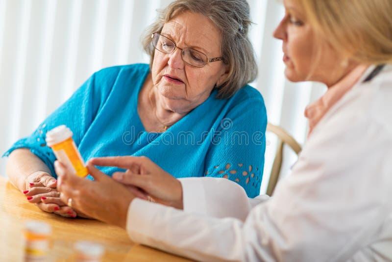 Doutor f?mea Talking com a mulher adulta superior sobre a prescri??o da medicina fotos de stock royalty free