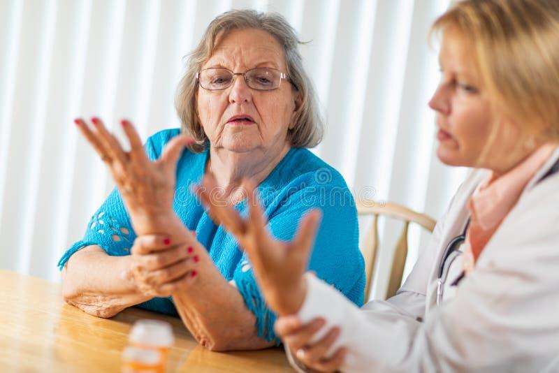 Doutor f?mea Talking com a mulher adulta superior sobre a terapia da m?o fotos de stock royalty free