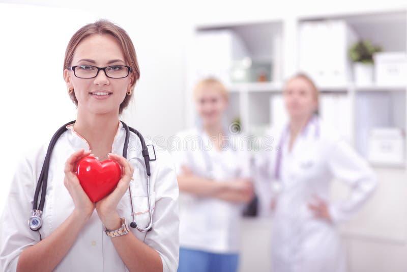 Doutor f?mea com o estetosc?pio que guarda o cora??o em seus bra?os Conceito dos cuidados m?dicos e da cardiologia na medicina imagem de stock