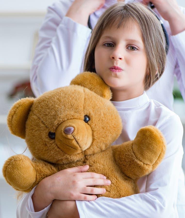 Doutor f?mea da mulher que examina a menina bonito pequena com urso do brinquedo imagens de stock royalty free