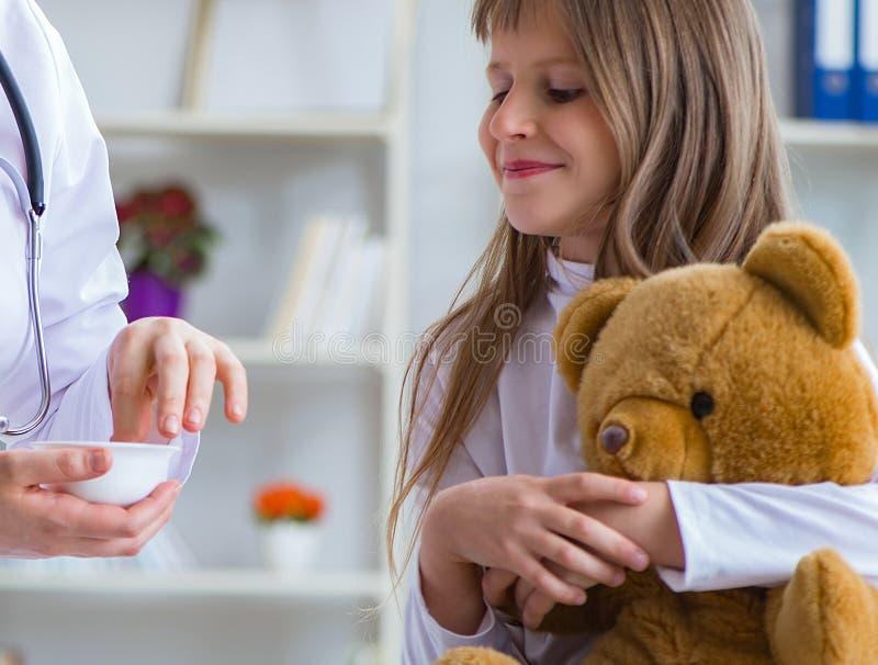 Doutor f?mea da mulher que examina a menina bonito pequena com urso do brinquedo imagem de stock royalty free