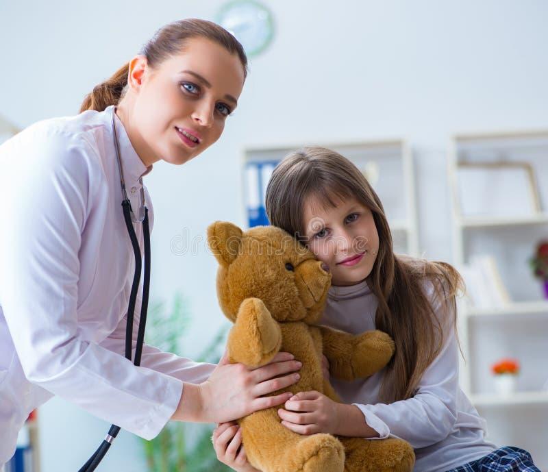 Doutor f?mea da mulher que examina a menina bonito pequena com urso do brinquedo imagens de stock