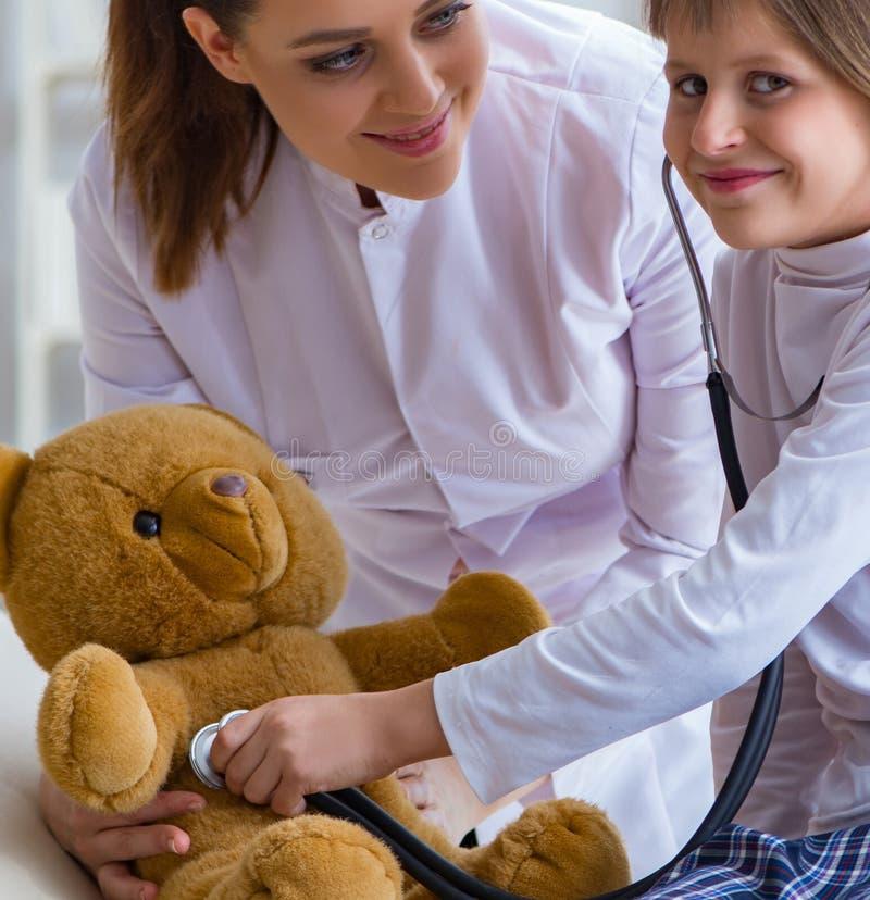 Doutor f?mea da mulher que examina a menina bonito pequena com urso do brinquedo fotos de stock royalty free