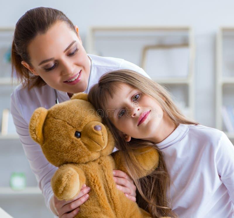 Doutor f?mea da mulher que examina a menina bonito pequena com urso do brinquedo fotos de stock