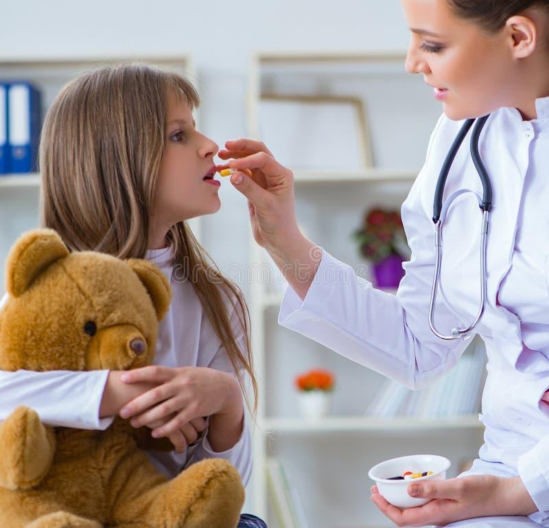 Doutor f?mea da mulher que examina a menina bonito pequena com urso do brinquedo fotografia de stock royalty free