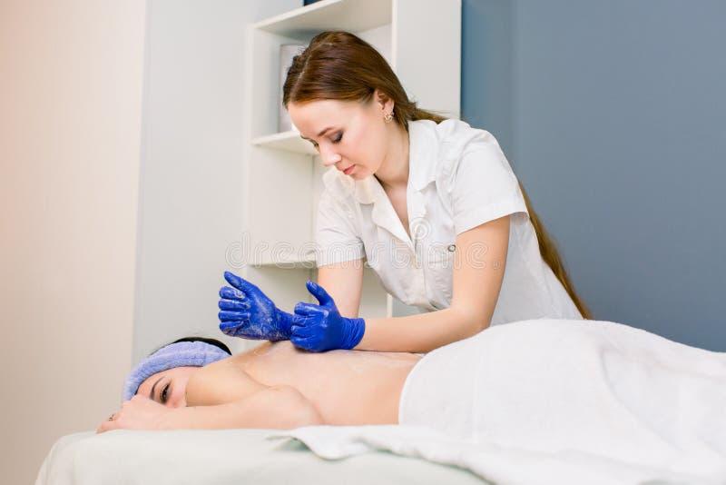 Doutor f?mea do esteticista com o paciente da mulher no centro do bem-estar dos termas O massagist profissional faz a massagem do foto de stock