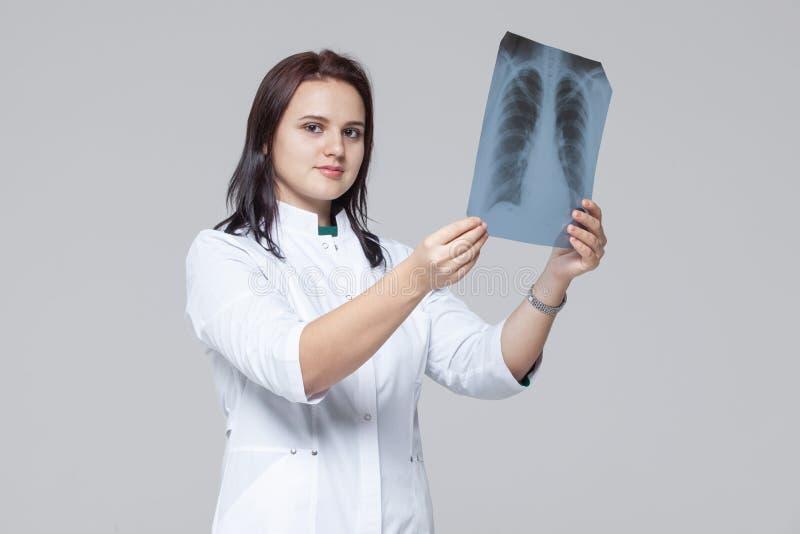 Doutor f?mea novo que olha a imagem do raio X dos pulm?es imagens de stock