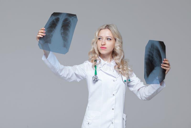 Doutor f?mea novo que olha a imagem do raio X dos pulm?es foto de stock