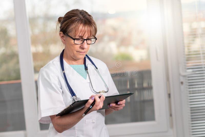Doutor f?mea que toma notas na prancheta fotografia de stock