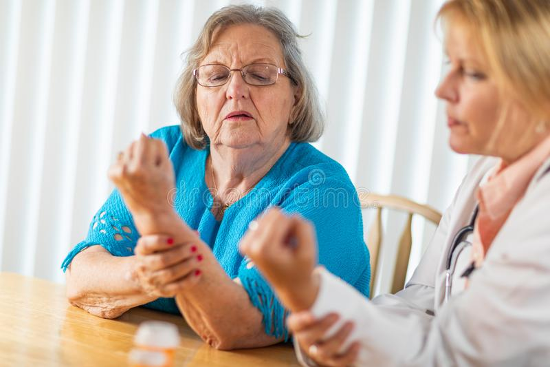 Doutor f?mea Talking com a mulher adulta superior sobre a terapia da m?o imagens de stock royalty free
