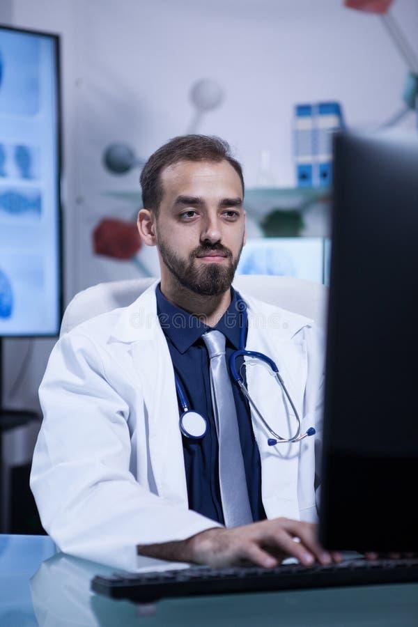 Doutor farpado novo considerável que datilografa em seu computador no escritório do hospital fotos de stock royalty free