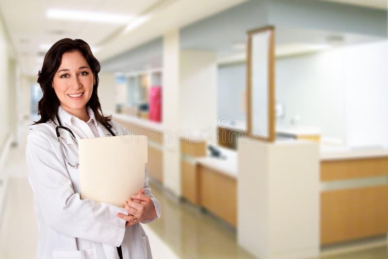 Doutor feliz com o arquivo da carta paciente no hospital imagens de stock royalty free