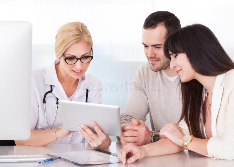 Doutor feliz Discussing With Couple imagem de stock