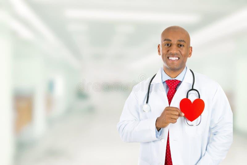 Doutor feliz que guarda o coração vermelho que está no corredor do hospital fotografia de stock royalty free