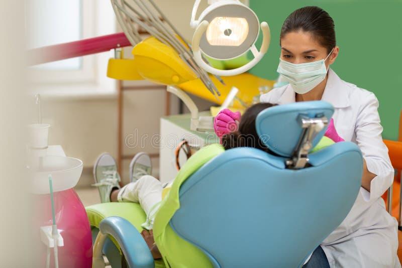 Doutor focalizado da mulher que inclina-se sobre um paciente novo imagem de stock