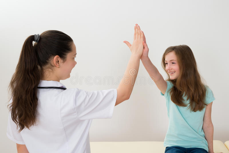 Doutor Giving High Five à menina fotos de stock royalty free