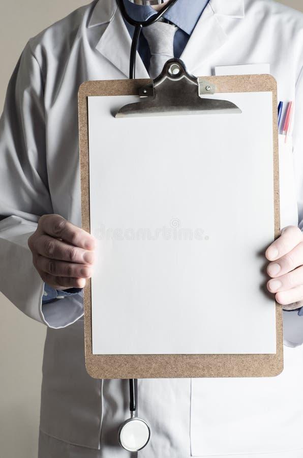 Doutor Holding Clipboard com a folha de papel vazia que enfrenta o visor imagem de stock