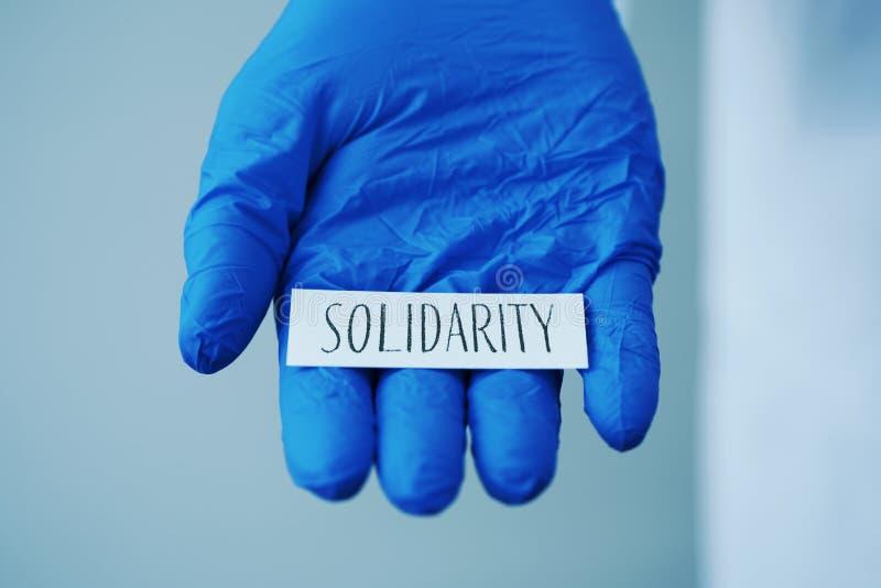 Doutor homem mostrando a palavra solidariedade em uma nota fotos de stock
