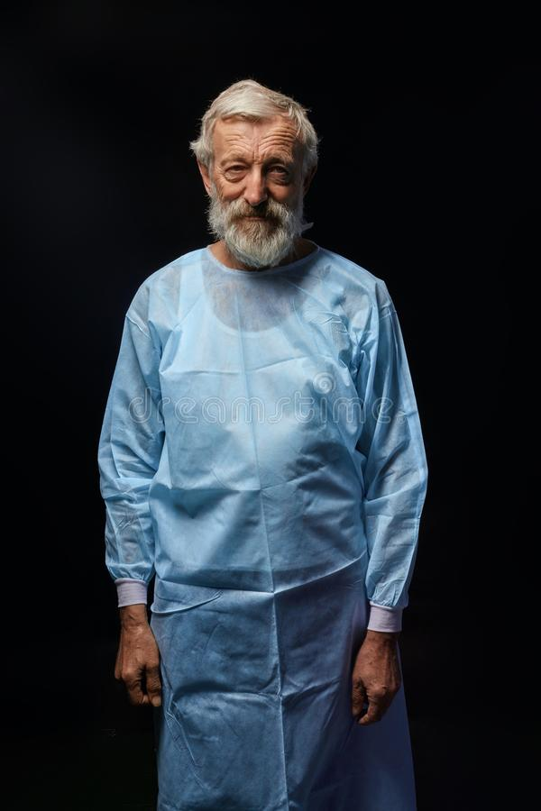 Doutor idoso considerável no uniforme especial que levanta à câmera imagens de stock royalty free