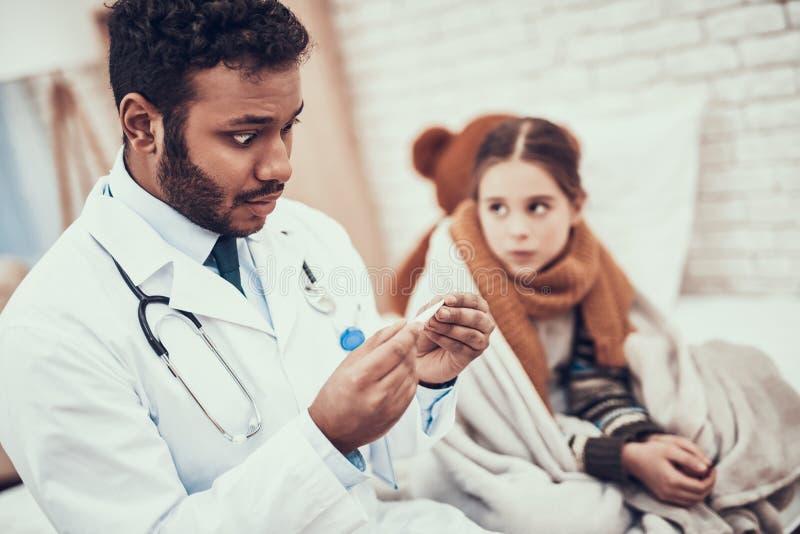 Doutor indiano que vê pacientes em casa O doutor está tomando a temperatura da menina com frio imagem de stock royalty free