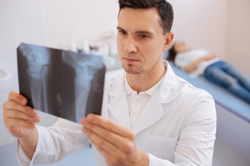 Doutor inteligente sério que olha a foto do raio de X fotos de stock