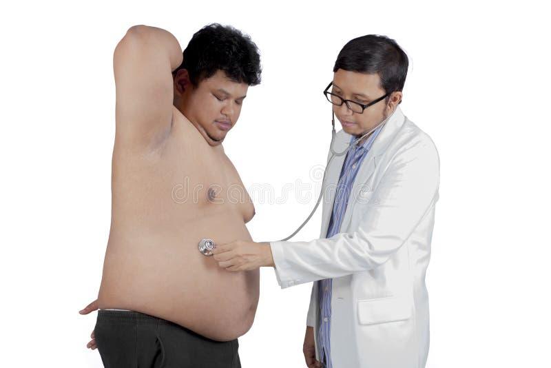 Doutor isolado que examina o paciente excesso de peso imagem de stock royalty free