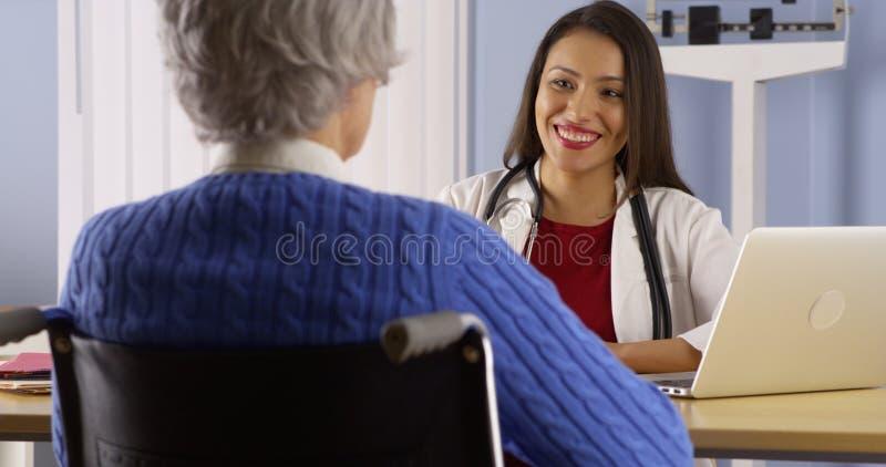 Doutor latino-americano feliz que fala com paciente superior fotografia de stock royalty free