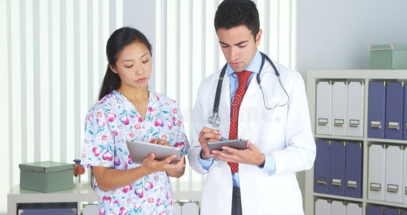 Doutor latino-americano que fala com a enfermeira asiática com tabuletas fotografia de stock