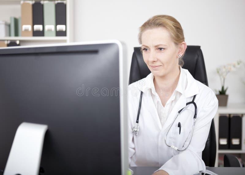Doutor Looking da mulher no monitor do computador seriamente foto de stock royalty free