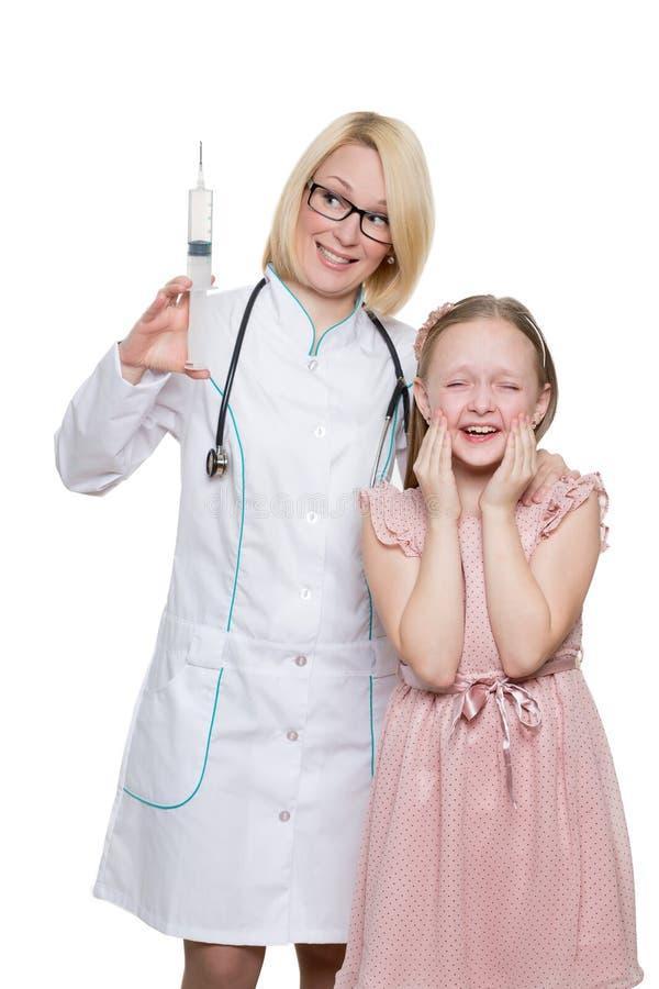 Doutor louco que faz a injeção vacinal a uma criança foto de stock