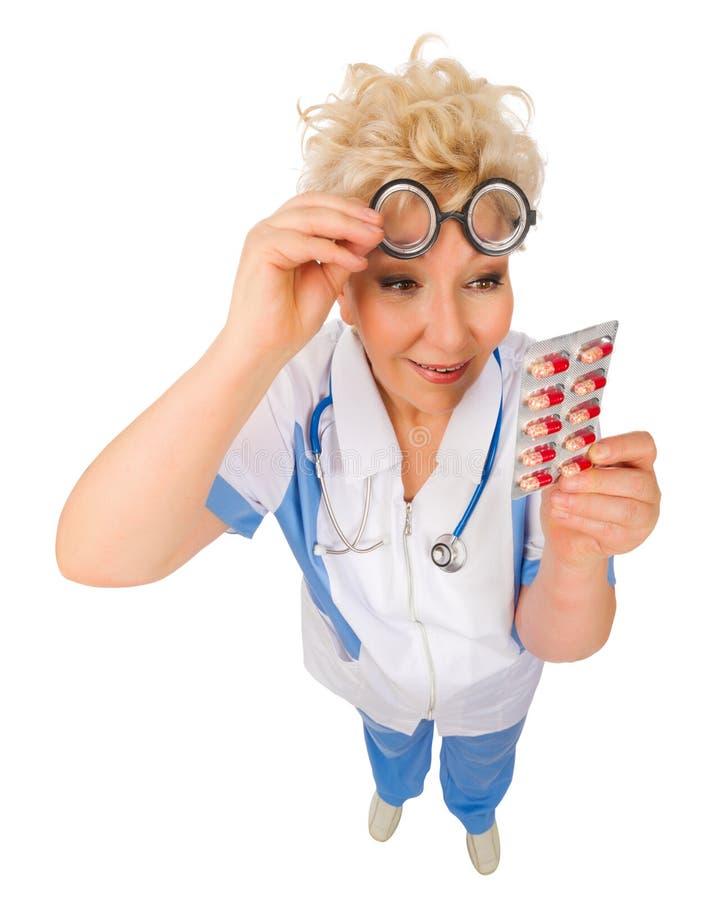 Doutor maduro engraçado em vidros do lerdo com comprimidos imagens de stock