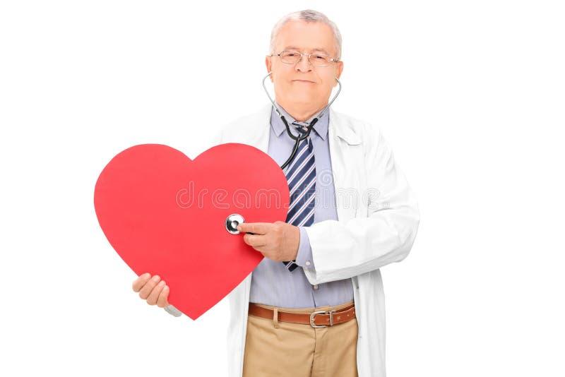 Doutor maduro que guarda o estetoscópio e um coração imagem de stock royalty free