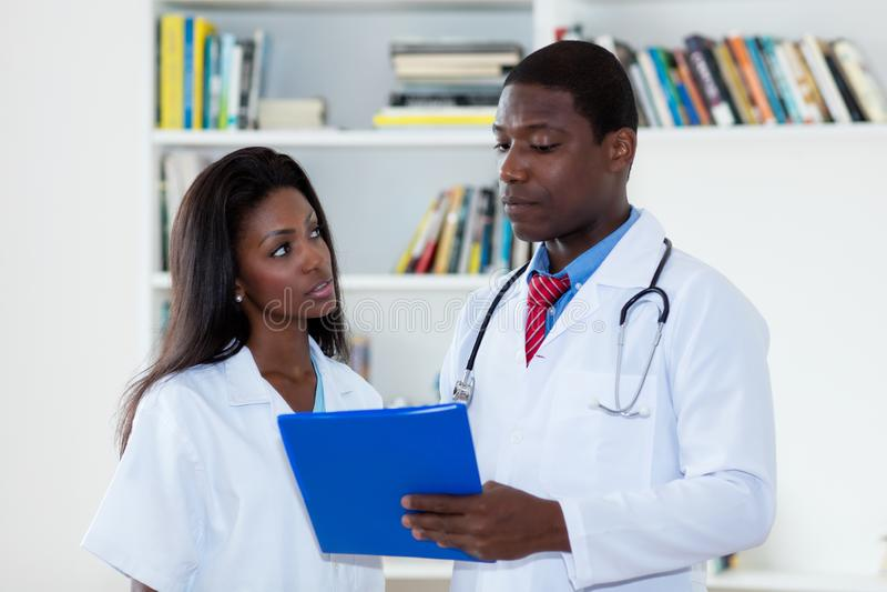 Doutor masculino afro-americano que fala com a enfermeira sobre o paciente imagens de stock