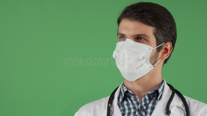 Doutor masculino alegre em uma máscara médica que sorri à câmera imagem de stock royalty free