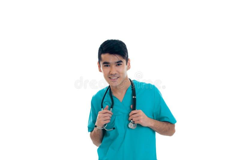 Doutor masculino alegre no uniforme com o estetoscópio em seu pescoço que sorri na câmera isolada no fundo branco imagem de stock